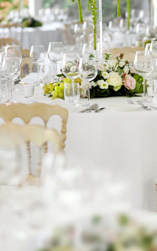 Formal table settings at a wedding venue with stylish white chairs, elegant glassware and silverware around floral centrepieces with selective focus to one table